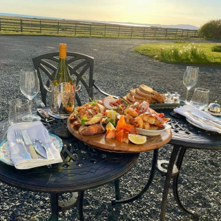 Our guests this evening opted to have their locally sourced seafood platter outside enjoying the view, sunset and off course with the current regulations a bottle of wine outside  How's this for a post lockdown meal?  #seafoodbythesea #sunset #islay #lobster #crab #shellfish #seafood #langoustine #salmon #bread #oatties #local #fresh  @visitscotland @corneyandbarrowayr